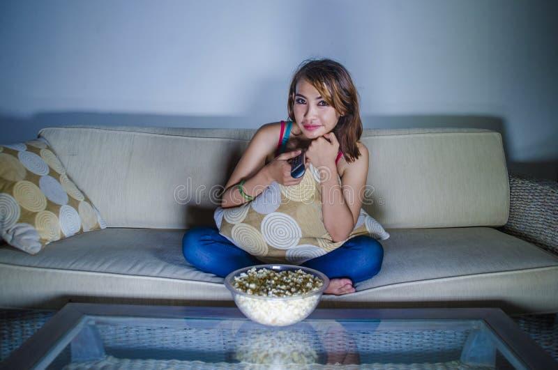 观看tel的年轻愉快的西班牙拉丁妇女在家沙发长沙发 库存照片