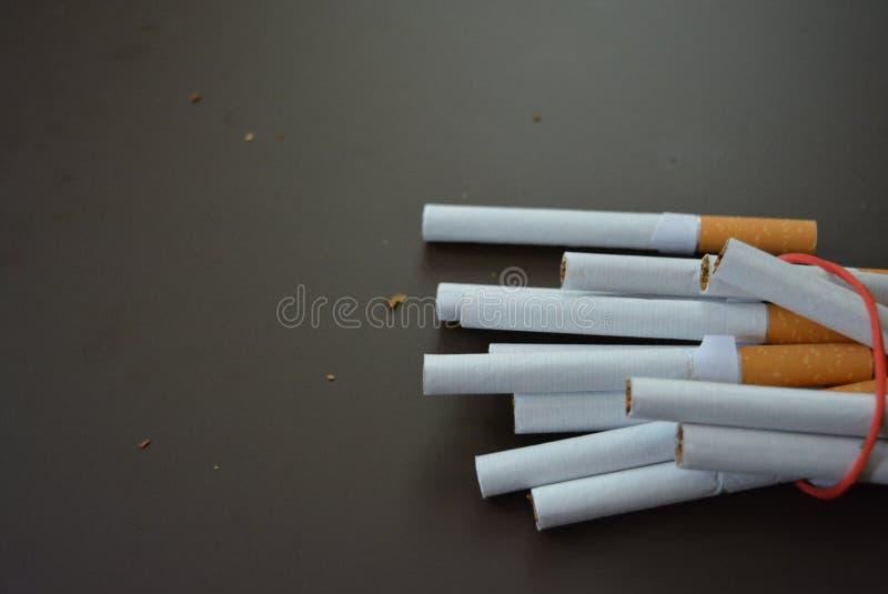规则香烟用烟草排行在一张棕色表面无光泽的桌上和栓与一个红色橡皮筋儿 图库摄影