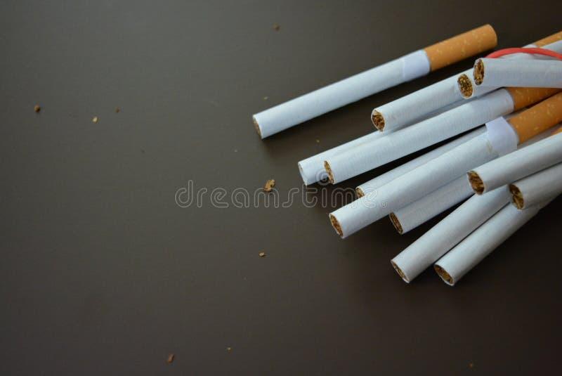 规则香烟用烟草排行在一张棕色表面无光泽的桌上和栓与一个红色橡皮筋儿 库存图片