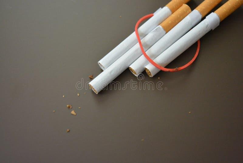 规则香烟用烟草排行在一张棕色表面无光泽的桌上和栓与一个红色橡胶禁令 库存图片