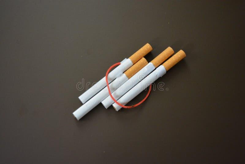 规则香烟用烟草排行在一张棕色表面无光泽的桌上和栓与一个红色橡胶禁令 免版税库存照片