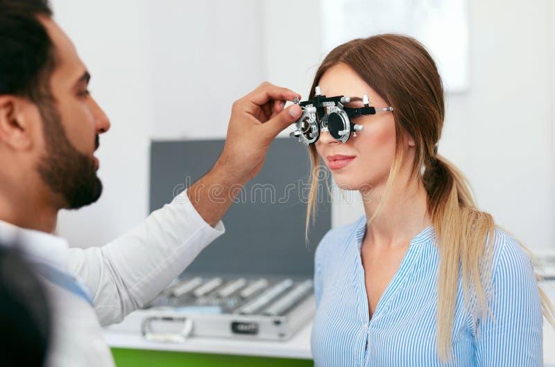 视力测定检查妇女眼力的测试眼科医生在诊所 免版税库存图片