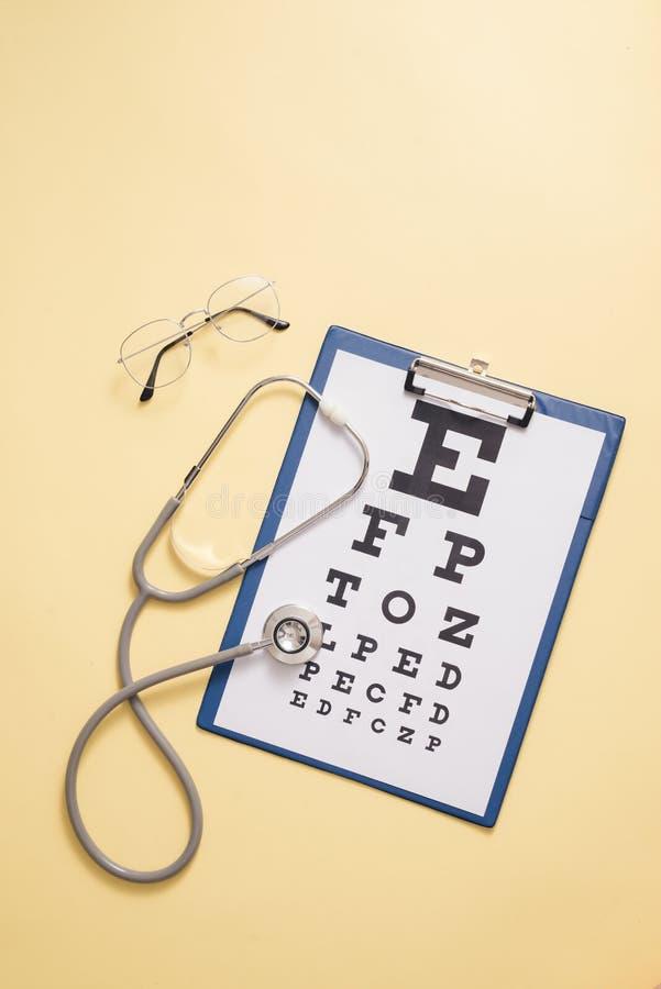 视敏度测试和医疗听诊器的表在黄色背景中 眼睛诊断,眼病的侦查的概念 库存图片