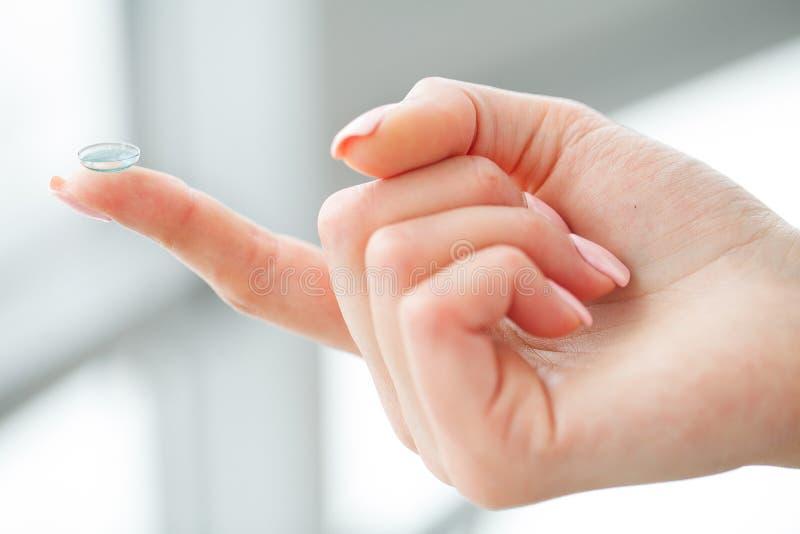视觉隐形眼镜 美丽的妇女握在联络的手指 免版税库存照片
