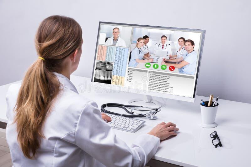 视讯会议医生与同事的在计算机上 库存照片