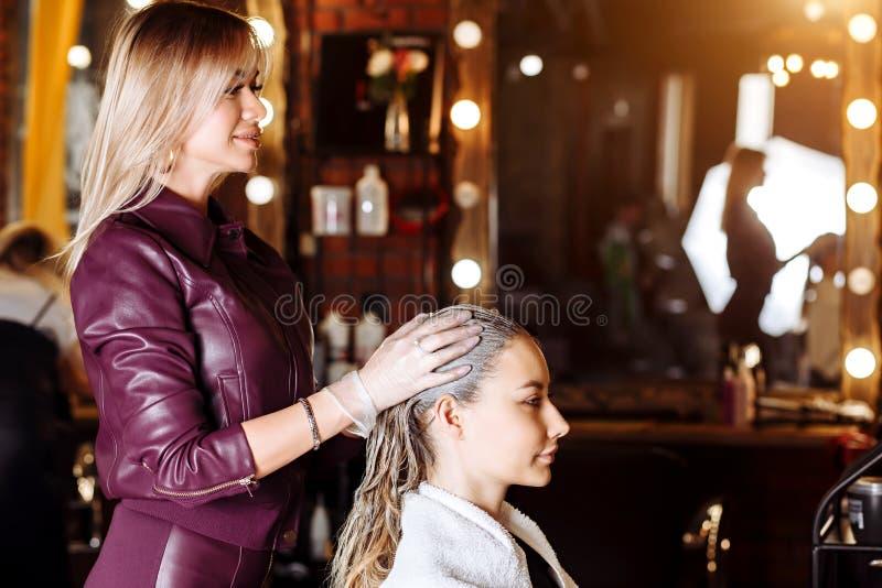 角质素调直,使光滑,头发染色和治疗 应用面具的专业女性美容师于女性顾客在 免版税库存图片