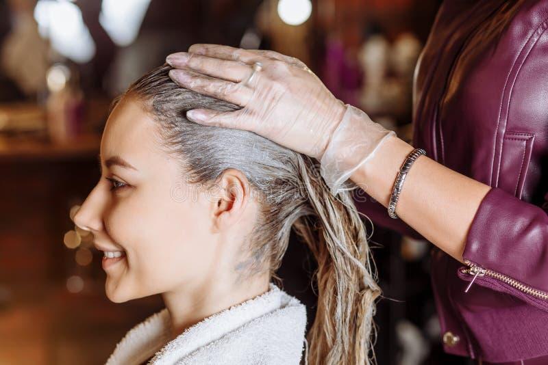 角质素调直,使光滑,头发染色和治疗 应用面具的专业女性美容师于女性顾客在 图库摄影