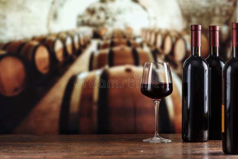 觚现有量品尝酒 有酒瓶和玻璃的葡萄酒库 spac 免版税库存照片
