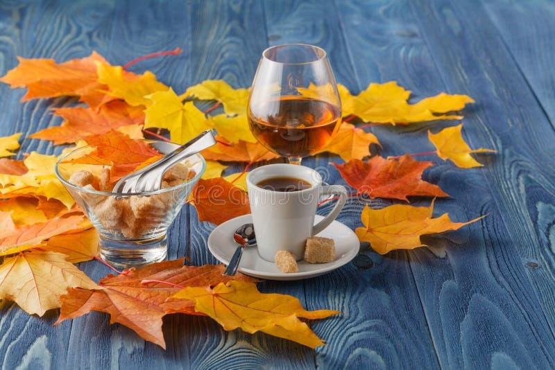 觚白兰地酒和杯子热的coffeeon木老桌面 免版税库存图片