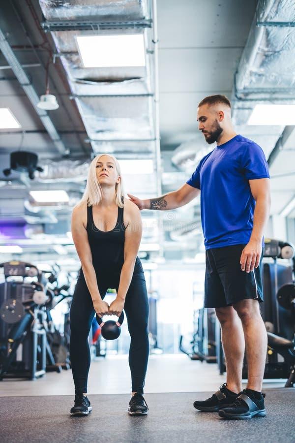 解决与个人教练员的妇女在健身房 图库摄影