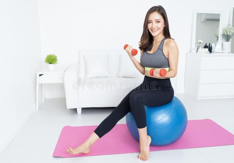 解决与哑铃的画象美丽的亚裔年轻运动的妇女坐体操蓝色适合的球和看照相机  库存照片