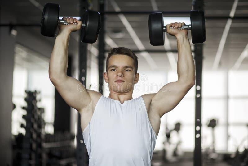 解决与哑铃重量的爱好健美者在健身房 做与哑铃的人爱好健美者锻炼 健身强健的身体 免版税库存图片