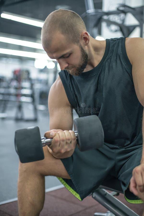 解决与哑铃重量的爱好健美者在健身房 做与哑铃的人爱好健美者锻炼 健身强健的身体 库存照片