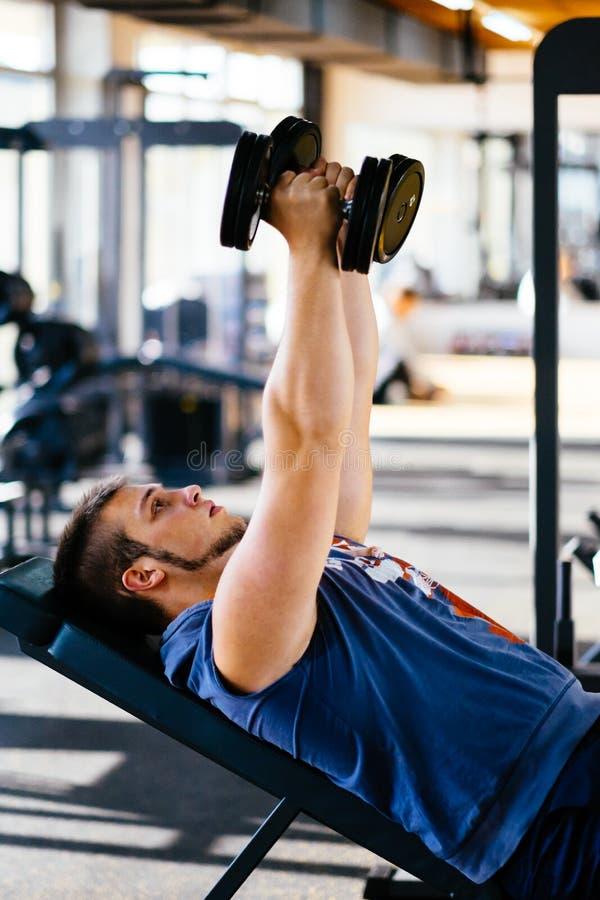 解决与在健身健身房的哑铃的年轻英俊的人 免版税图库摄影