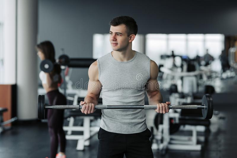 解决与在健身房的哑铃的英俊的肌肉人 库存图片