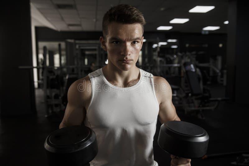 解决与在健身房的哑铃的被集中的年轻健身人 库存照片
