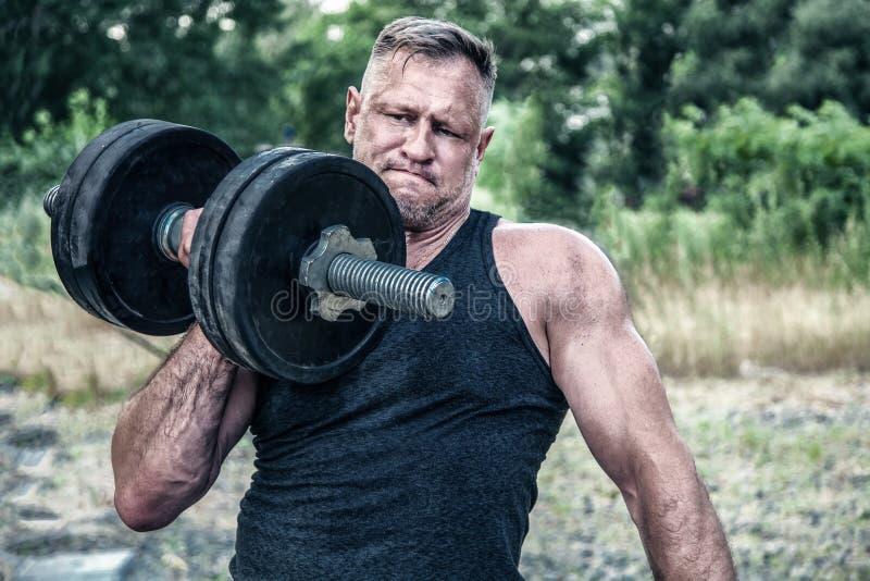 解决与在街道健身房前面的一个哑铃的运动人 E 室外锻炼 的锻炼 库存图片