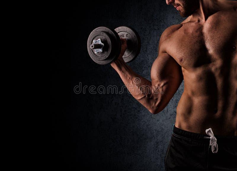 解决与在黑色后面的哑铃的英俊的肌肉人 免版税库存照片