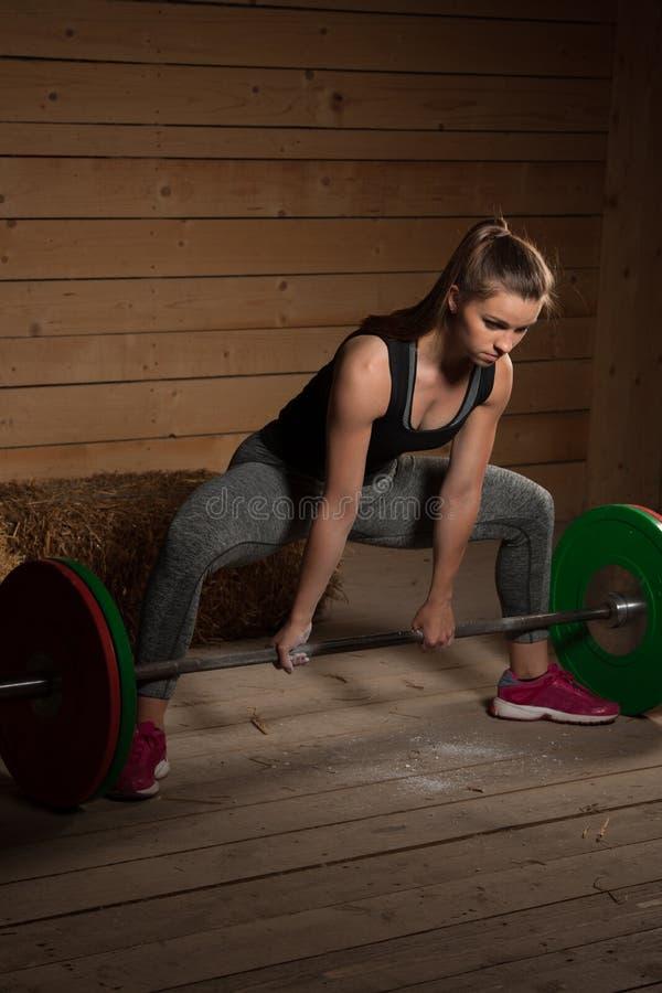 解决与杠铃的活跃女子运动员- powerlifting 免版税库存图片