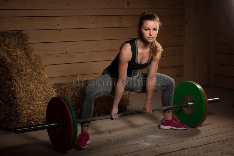解决与杠铃的活跃女子运动员- powerlifting 库存照片