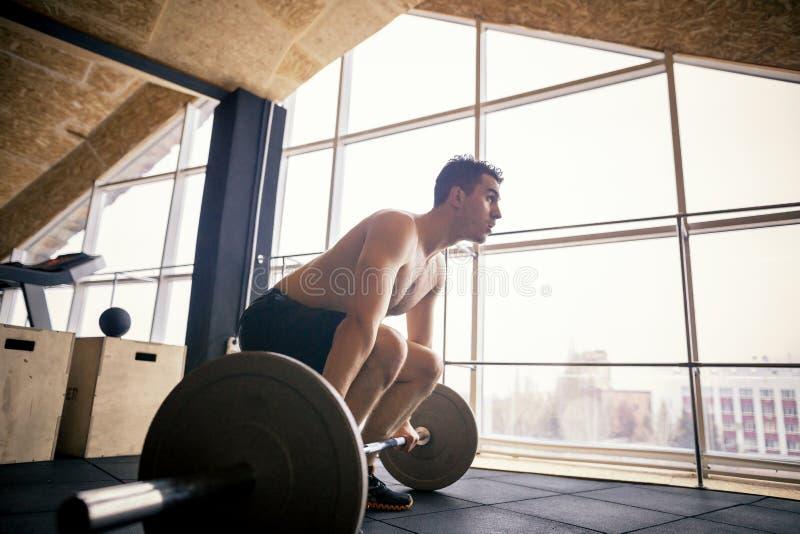 解决与杠铃的适合的年轻人在健身房 爱好健美者女性行使在健身房 库存图片
