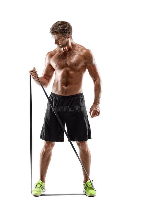 解决与橡皮筋儿,演播室射击的英俊的健身人 免版税图库摄影