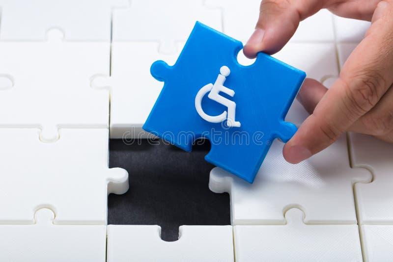 解决与蓝色片断的人的手拼图 免版税图库摄影