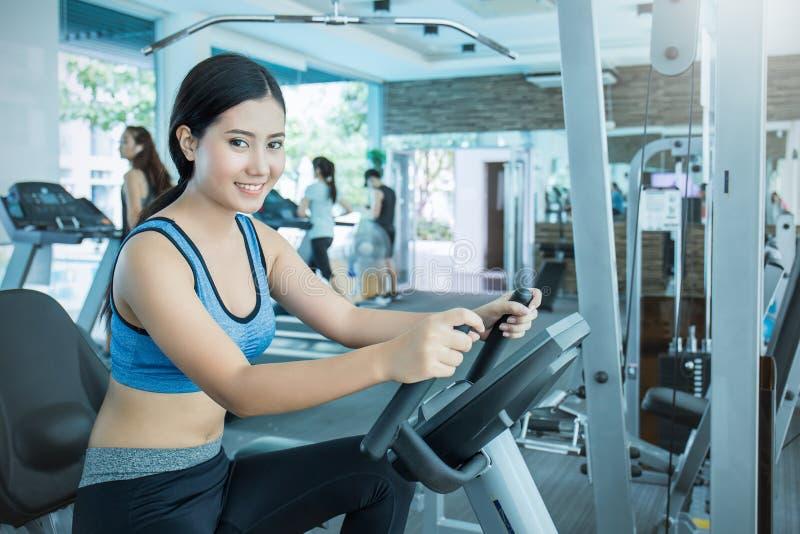 解决与锻炼机器的可爱的年轻亚裔妇女在健身房 免版税库存照片