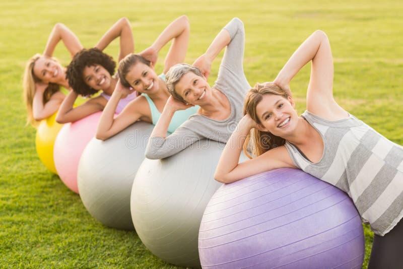 解决与锻炼球的微笑的运动的妇女 免版税库存图片