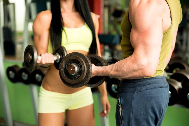 解决在与哑铃的健身房的健身夫妇 库存图片