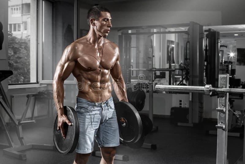 解决在与杠铃,形状胃肠的健身房的肌肉人 强的男性赤裸躯干吸收 库存图片