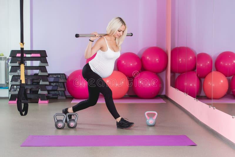解决在与球的健身房的秀丽运动的孕妇在背景 免版税库存图片