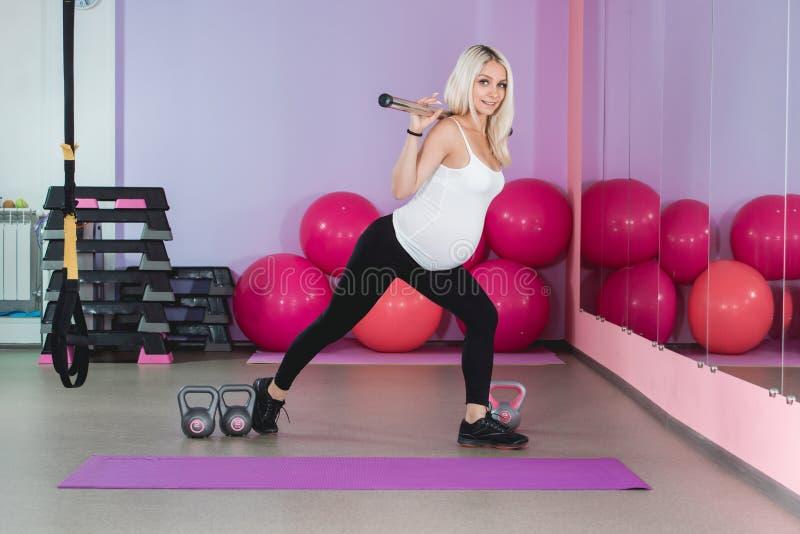 解决在与球的健身房的秀丽运动的孕妇在背景 库存照片