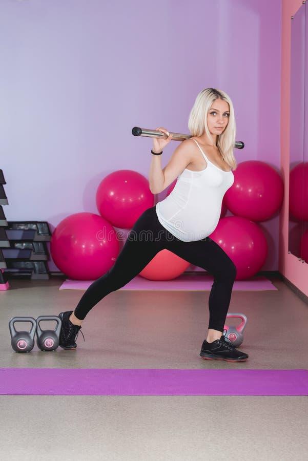 解决在与球的健身房的秀丽运动的孕妇在背景 图库摄影