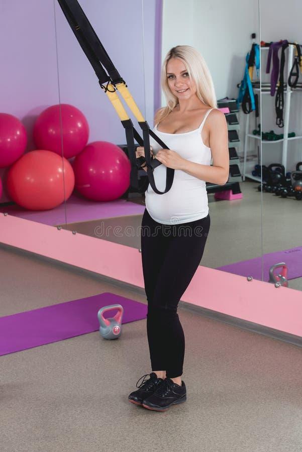 解决在与球的健身房的秀丽运动的孕妇在背景 库存图片