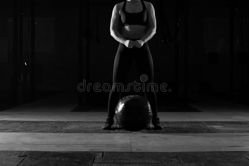 解决在与重球的健身房的肌肉妇女 库存图片