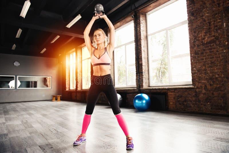 解决在与kettlebell的健身房的白肤金发的女孩 Crossfit锻炼 库存图片