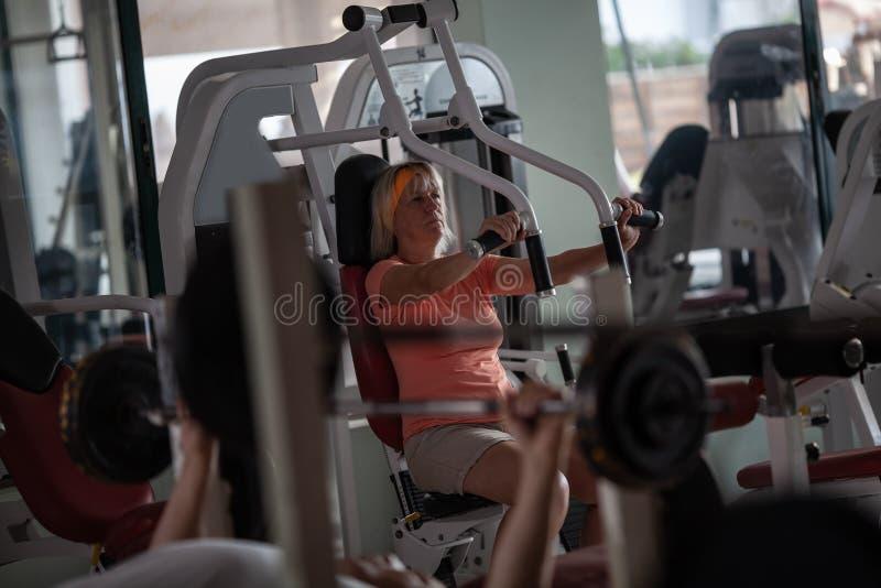 解决在健身房的一名金发资深妇女 免版税库存图片