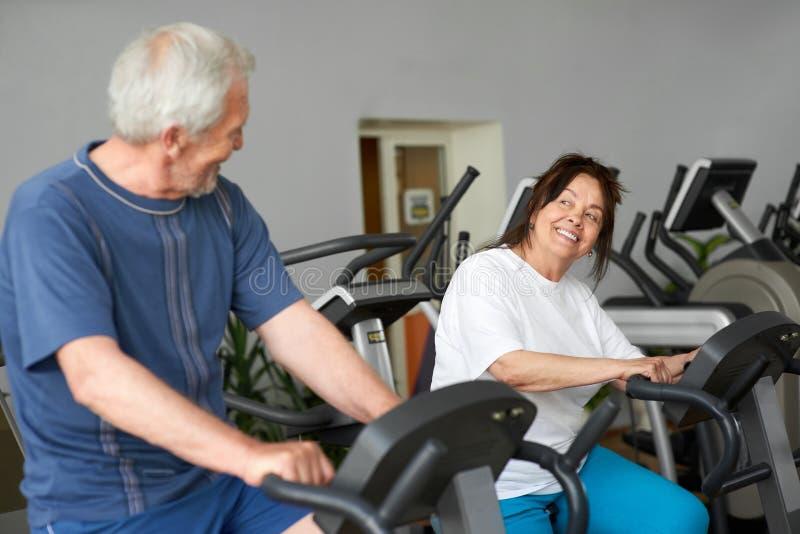 解决在健身房的前辈美好的夫妇  免版税图库摄影