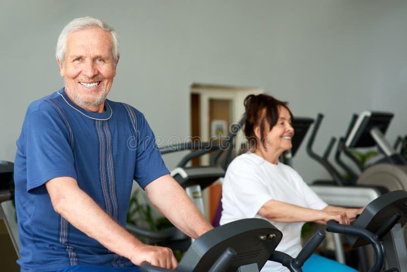 解决在健身房的愉快的年长人 免版税库存图片