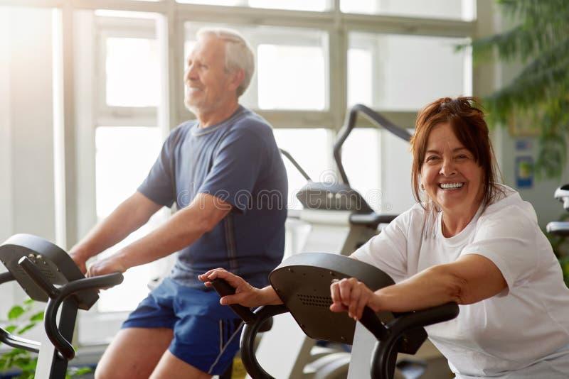 解决在健身房的愉快的资深妇女 库存图片