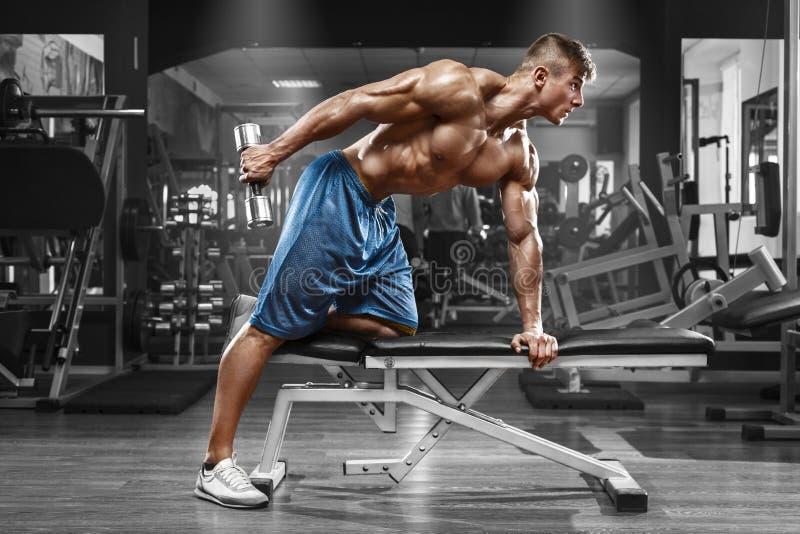 解决在健身房的肌肉人做与哑铃的锻炼在三头肌,强的男性赤裸躯干吸收 图库摄影