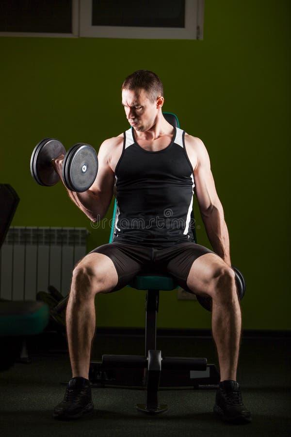 解决在健身房的肌肉人做与哑铃,爱好健美者男性赤裸躯干的锻炼 免版税图库摄影