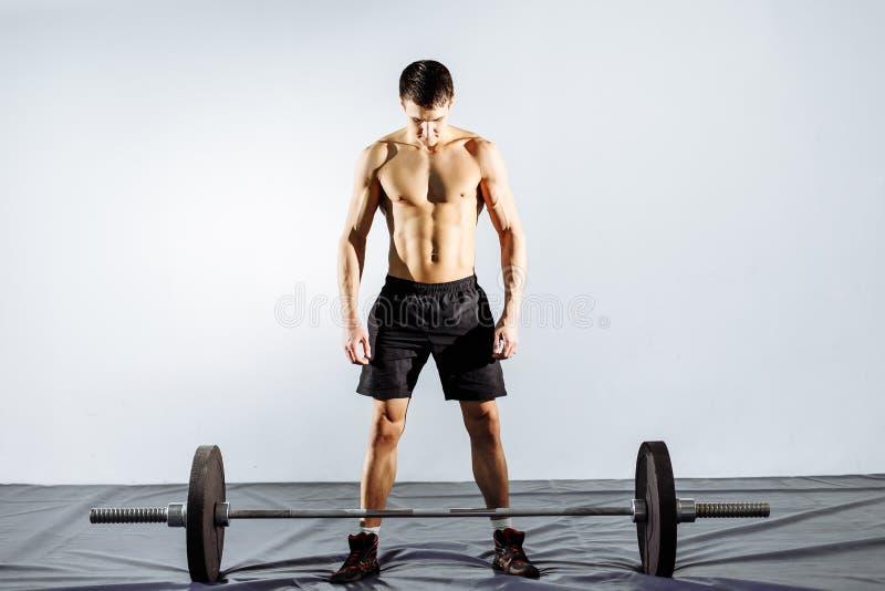 解决在健身房的肌肉人做与杠铃,强的男性赤裸躯干吸收的锻炼 免版税图库摄影
