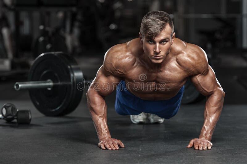 解决在健身房的肌肉人做俯卧撑锻炼,强的男性赤裸躯干吸收 库存图片