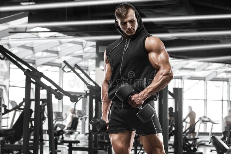 解决在健身房的肌肉人做锻炼,坚强的男性爱好健美者 免版税库存图片