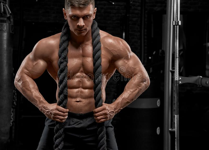 解决在健身房的肌肉人做锻炼 免版税库存照片