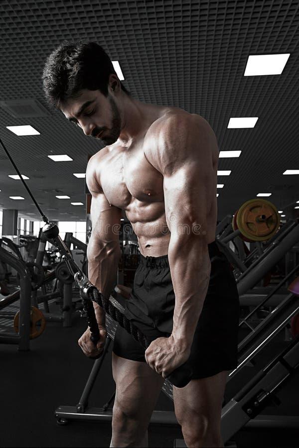 解决在健身房的肌肉人做锻炼在三头肌 免版税库存图片