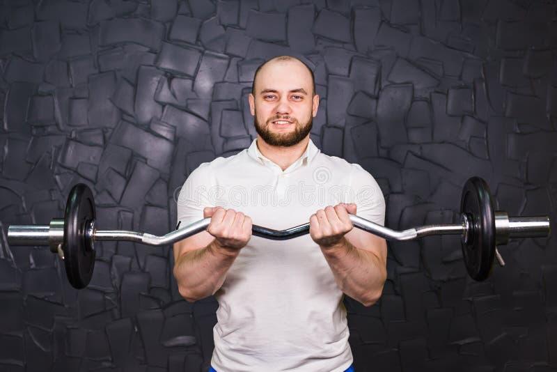 解决在健身房的肌肉人做锻炼,与杠铃的强的男性 免版税库存照片