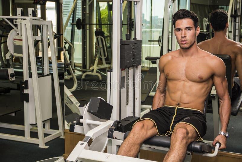 解决在健身房设备的赤裸上身的年轻人 库存照片